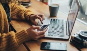 Femme dans un café avec ordinateur et carte bancaire